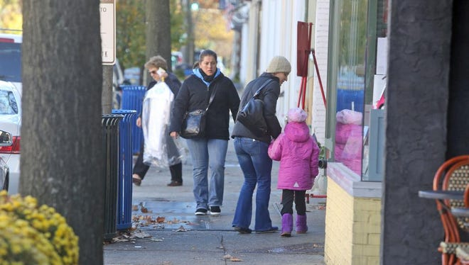 People walk along Purchase St. in Rye Nov. 18, 2014. Rye will taking part in Small Business Saturday, which this year will be on Nov. 29th, encouraging people to shop local.