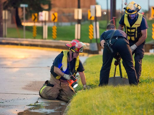 In this June 30, 2014 photo Cedar Rapids firefighters open a storm sewer cover as they search for a teenager who was swept away in a storm drain after heavy rainfall overwhelmed the eastern Iowa city's storm sewer system. Officials say Logan Blake, 17, was swept away by the fast-moving water in the drain at an elementary school around 7:20 p.m. Monday.