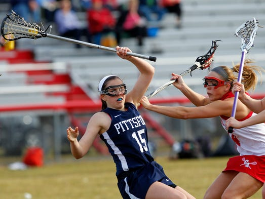 Pittsford's Allie Panara, left, is checked to the ground by Canandaigua's Sydney Reber during girls lacrosse action between the Pittsford Panthers and Canandaigua Braves in Canandaigua Thursday evening, April 10, 2014.