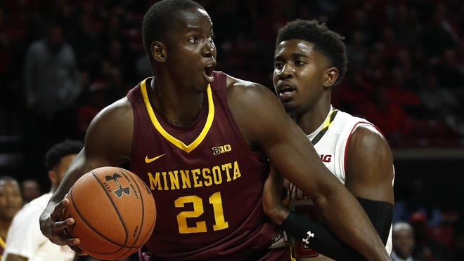 Minnesota center Bakary Konate looks for a teammate as he is pressured by Maryland guard Darryl Morsell, right, during the first half of an NCAA college basketball game in College Park, Md., Thursday, Jan. 18, 2018. (AP Photo/Patrick Semansky)