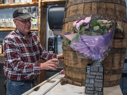 JB's Whiskey Creek Old Style Grill owner Jim Bloomfield pours a shot of Jack Daniels whiskey from a barrel in his new restaurant at 3905 W. Dickman Road in Springfield.