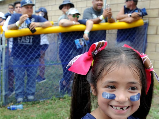 Diana Moreno smiles at some of the Dallas Cowboy players