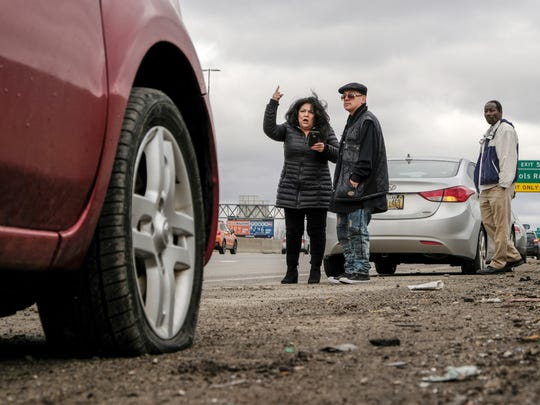 Sylvia Campos of Detroit gets upset while watching traffic from the side of northbound I-75 near the McNichols Rd. exit with her boyfriend Rolando Lopez of Saginaw, after hitting a pothole that left her front passenger side tire flat on Wednesday, February 21, 2018 in Detroit.