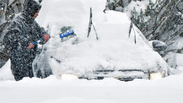 A man sweeps snow off of his car during a snow storm on Saturday, Jan. 23, 2016.