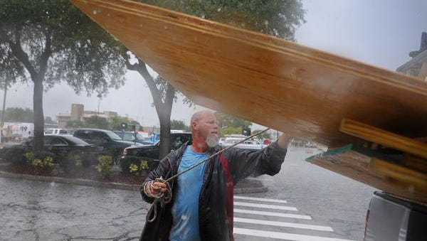 Paul Poulakis of Merritt Island loads up plywood as concern Brevard residence brave torrential rain storms to prepares for hurricane Matthew as they pack home Depot on Merritt Island Tuesday afternoon to buy plywood to protect their homes .