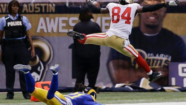 San Francisco 49ers wide receiver Brandon Lloyd (84) jumps into the end zone ahead of St. Louis Rams cornerback Janoris Jenkins on an 80-yard pass play in the second quarter on Monday, Oct. 13, 2014, in St Louis.