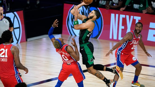 Boston Celtics' Jayson Tatum, right, goes up for a shot over Philadelphia 76ers' Josh Richardson (0) during the second half of an NBA basketball first round playoff game Monday, Aug. 17, 2020, in Lake Buena Vista, Fla. The Celtics won 109-101.
