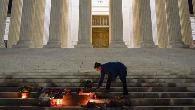 People lay flowers and light candies outside the Supreme Court Friday, Sept. 18, 2020, in Washington, after the Supreme Court announced that Supreme Court Justice Ruth Bader Ginsburg died of metastatic pancreatic cancer at age 87.