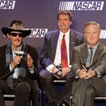 Team owner Richard Petty, left, speaks as NASCAR Chairman and CEO Brian France, right, and NASCAR president Mike Helton, back, listen during a news conference in Charlotte, N.C., Tuesday. NASCAR announced a new charter system for team owners.