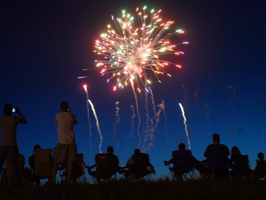 Spectators watch Sioux Falls Jaycees Fourth Of July fireworks from the bike path near the W.H. Lyon Fairgrounds in 2016.