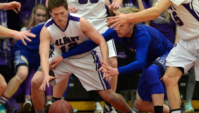 Albany's Kyle Birr (12) battles Braham's Connor Tschumper (0) for a loose ball in the first half of the Section 6-2A championship game Friday night at Halenbeck Hall.
