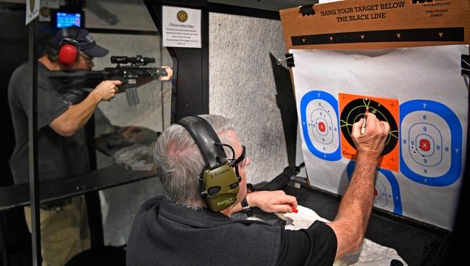 Mark Bradshaw, left, takes some shots as Doug Fleming marks his target while they practice at Royal Range in West Nashville.Thursday March 1, 2018, in Nashville, Tenn