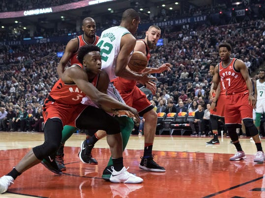 Toronto Raptors OG Anunoby, left, and Jonas Valanciunas, right, crowd out Boston Celtics Al Horford during the first half of an NBA basketball game Tuesday, Feb. 6, 2018, in Toronto. (Chris Young/The Canadian Press via AP)