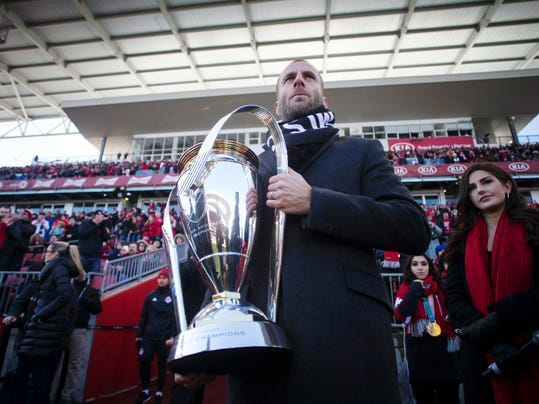 Former Toronto FC player Benoit Cheyrou carries the MLS trophy onto the field before Toronto's season opening MLS soccer game against the Columbus Crew in Toronto on Saturday, March 3, 2018. (Chris Young/The Canadian Press via AP)