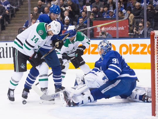 Toronto Maple Leafs goaltender Frederik Andersen (31) clears the puck in front of Dallas Stars left wing Jamie Benn (14) and Maple Leafs defenseman Ron Hainsey (2) during the first period of an NHL hockey game Wednesday, March 14, 2018, in Toronto. (Chris Young/The Canadian Press via AP)