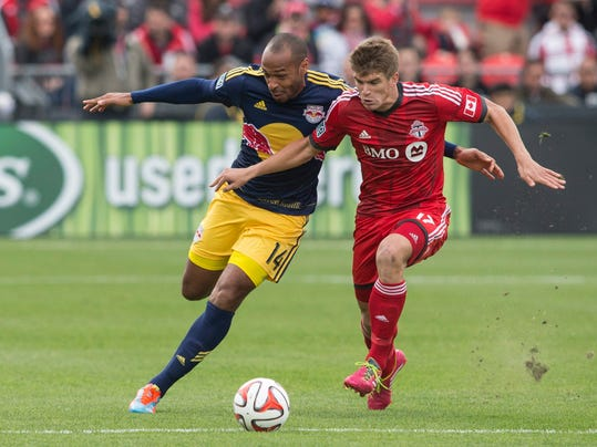 Toronto FC's Nick Hagglund, right, tussles with New York Red Bulls' Thierry Henry  during the first half of an MLS soccer game in Toronto on Saturday, May 17, 2014. (AP Photo/The Canadian Press, Chris Young)