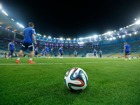 A 2014 World Cup official soccer ball, called Brazuca, sits on the sidelines as Bosnia-Herzegovina players pass the ball, background, during a training session at the Maracana Stadium in Rio de Janeiro, Brazil, Saturday, June, 14, 2014. Bosnia-Herzegovina will face Argentina in group F of the 2014 soccer World Cup at the stadium on Sunday. (AP Photo/Victor R. Caivano)