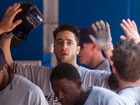 Milwaukee Brewers Ryan Braun celebrates in the dugout after scoring on a sacrifice fly by Jonathan Lucroy during third inning interleague baseball action against the Toronto Blue Jays in Toronto on Wednesday July 2 , 2014. (AP Photo/The Canadian Press, Chris Young)