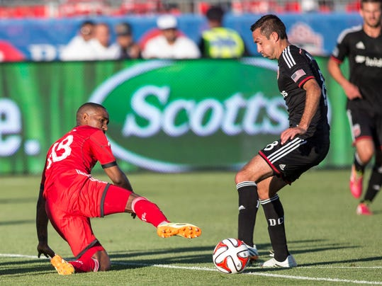 Toronto FC 's Jermain Defoe, left, battles for the ball with D.C. United's Davy Arnaud during the first half of an MLS soccer game in Toronto on Saturday, July 5, 2014. (AP Photo/The Canadian Press, Chris Young)