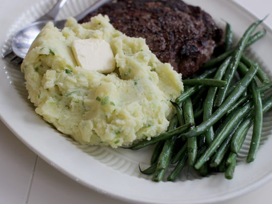 ... mashed potatoes flecked with scallions and topped with butter in