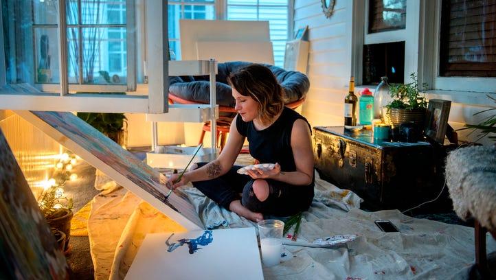 Jill Freitas works on one of her paintings in enclosed