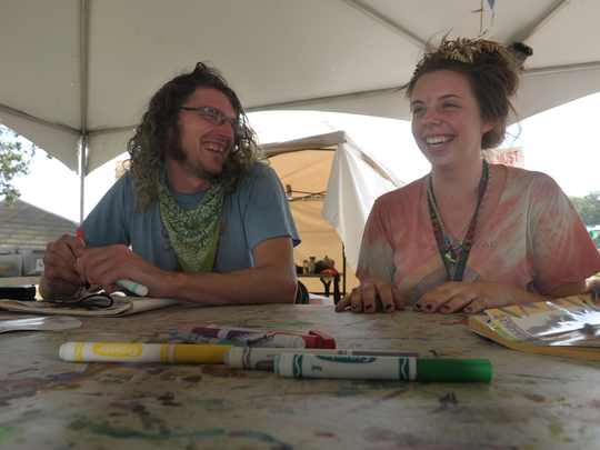 Ira Alsept, left, and Brianna Reynolds, volunteers for Dayton, Ohio not-for-profit Kidz Jam, sit under the tent at Bonnaroo Music and Arts Festival on Friday June 12, 2015..