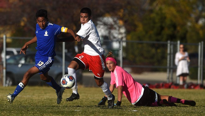 Wooster's Miguel Villalobos (2) gets past Reed goalie Hunter Ehlers during their soccer game in Reno on Oct. 31, 2017.