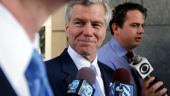 Former Virginia Gov. Bob McDonnell, center, leaves the federal courthouse in Richmond, Va., on Wednesday, Aug. 13, 2014, on day 13 of the corruption trial of McDonnell and his wife, Maureen.