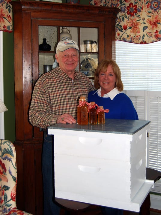 Butch and Maryann Wainscott display one of their beehives along with bottles.jpg