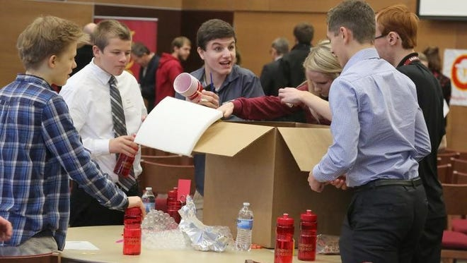 Left and below: Teams of high school students look through a box of miscellaneous items from which they will have to create a product to market.