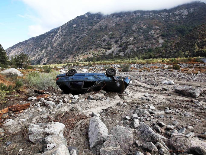 A car lies upside down after being swept down a wash in the mountain community of Forest Falls in the San Bernardino Mountains. Crews cleared roads in an area where some 2,500 people were stranded after thunderstorms caused mountain mudslides in Southern California over the weekend.