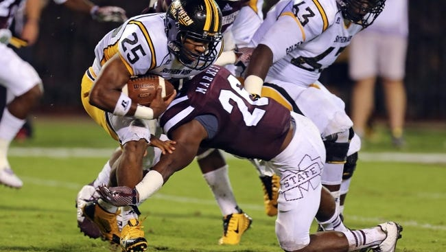 Aug 30, 2014; Starkville, MS, USA; Southern Miss Golden Eagles running back George Payne (24) runs the ball and is tackled by Mississippi State Bulldogs defensive back Kendrick Market (26) during the game at Davis Wade Stadium.  Mississippi State Bulldogs defeat the Southern Miss Golden Eagles 49-0. Mandatory Credit: Spruce Derden-USA TODAY Sports