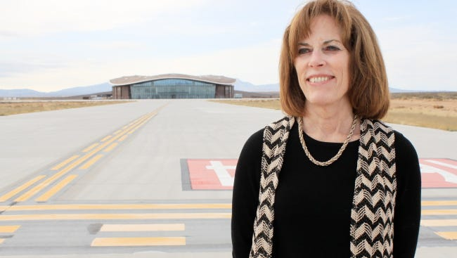 In this file photo, Christine Anderson, executive director of the New Mexico Spaceport Authority, stands in front of the spaceport hangar.