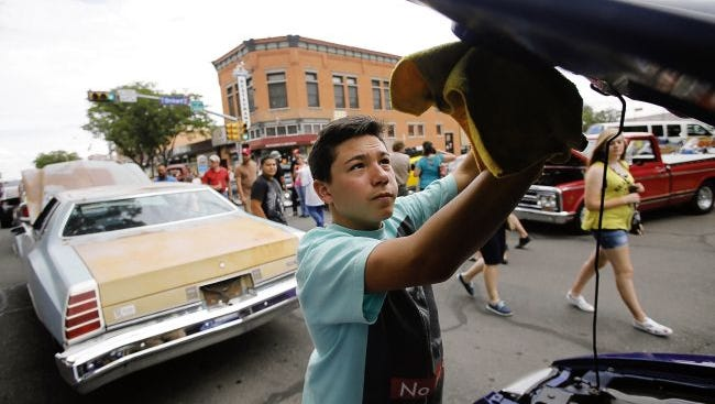 Samuel Ortiz cleans his uncle's 2003 Ford Mustang during the annual 2015 Rod Run Show N' Shine Block Party in downtown Farmington. The event returns this weekend.