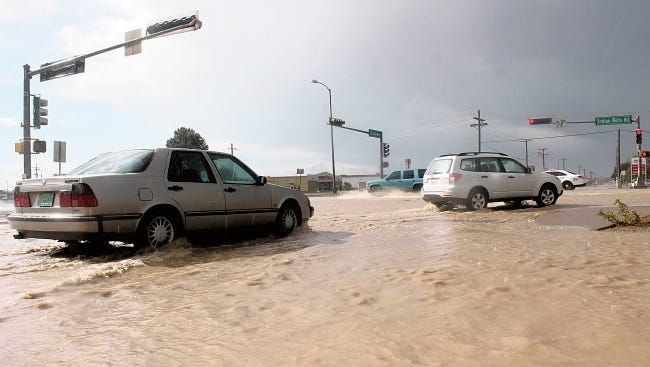 In this file photo, cars drive through a flooded street in Alamogordo.