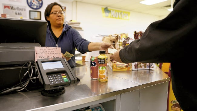 Cashier Vanessa Rodriguez works the register at the Quick Stop gas station and convenience store in Shiprock on Nov. 21, 2014. The Navajo Nation will increase its sales tax on July 1.