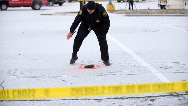 A sheriff's deputy marks evidence at the scene where a 4-year-old girl died after being struck by a vehicle while walking to school with her mother, Feb. 9, 2017.