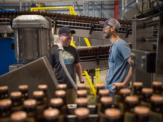 Dan Buzard and Evan Ide perform maintenance on the bottling line at Odell Brewing Co. Wednesday in Fort Collins. Odell's employee stock ownership plan makes employees like Buzard and Ide part-owners of the brewery.