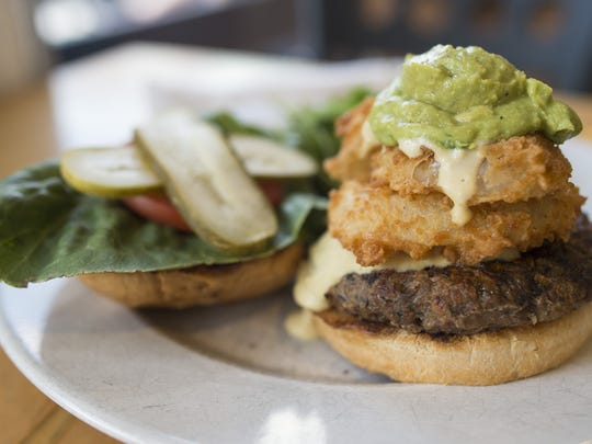 "Cashew cheese drizzles down the ""Ultimate Supreme Mega Burger"" at Tasty Harmony on Thursday, June 22, 2017. The vegetarian and vegan restaurant, located at 160 W. Oak Street, serves the burger with a soy, bean and rice patty."