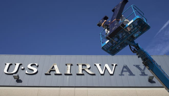 Summit West Signs employees take down the US Airways signage, October 15, 2015, at the US Airways hangar, Phoenix Sky Harbor International Airport, 4000 E. Sky Harbor Boulevard, Phoenix.  The signs will be changed to All American Airlines.