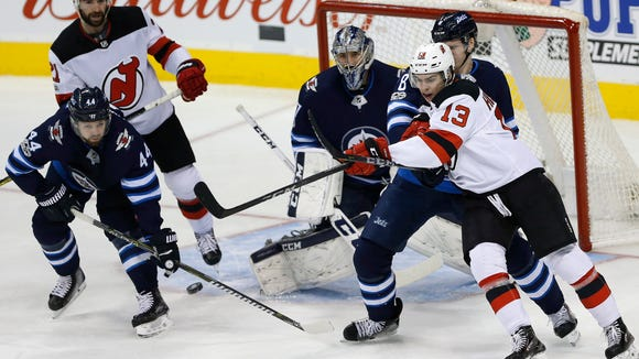 Winnipeg Jets' Jacob Trouba (8) and New Jersey Devils' Nico Hischier (13) fight for position in front of Jets goaltender Connor Hellebuyck (37) during the first period of an NHL hockey game in Winnipeg, Manitoba, Saturday, Nov. 18, 2017. (John Woods/The Canadian Press via AP)