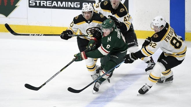 Minnesota Wild forward Ryan Donato (6) passes away from Boston Bruins Connor Clifton (75), Danton Heinen (43) and Trent Frederic (82) during the third period of an April 2019 game in St. Paul, Minn.