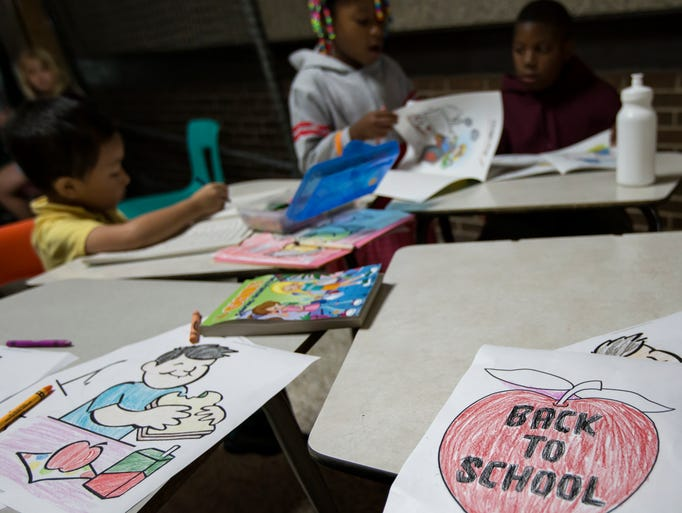 "With the first day of school being a few weeks away, families attend a ""Back to School Fair"" at Oshkosh North High School collecting school supplies, clothes, and hygiene products. In the background Zing Chang, Antaria Sandel, and James Pointer work on coloring books waiting for their turn for a hair cut."