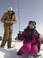 In this 1999 file photo, Sarah Beese, of Rib Mountain, tries her luck in the Wausau Noon Optimist Club Youth Fisheree on Lake Wasuau with her day father, Rick.