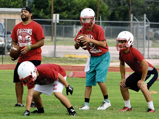 Matt Hollinshead — Current-Argus Loving senior quarterback Joel Hernandez, middle, looks down the left side before snapping the ball at practice Monday, Aug. 3.