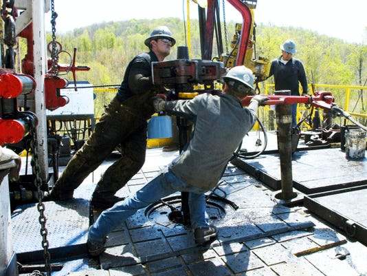 In this April 23, 2010, file photo, workers move a section of well casing into place at a Chesapeake Energy natural gas well site near Burlington in Bradford County. Drillers have paid nearly 1 billion in Pennsylvania impact fees over five years.