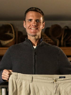 Brian Flemming holds up a pair of the 60-inch-waist pants he was wearing about two years ago, when he weighed 625 pounds. With a friend encouraging him, Flemming kicked alcohol, ate better and got active. He will run his first half-marathon in Detroit on Sunday.