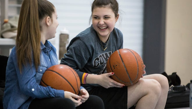 Lauren McGlaughlin talks with Sami Stanley during Cowan Middle School's girls basketball practice Tuesday evening. Lauren has been struggling with postural orthostatic tachycardia syndrome, a condition she was able to combat after several major fundraisers by the community allowed her to seek treatment at the Mayo Clinic in Rochester, Minnesota.