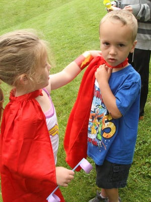 """Even superheroes need help, now and then. Super Kailey, Kailey Lowe left, helps adjust the cape fellow superhero Carter Costa during a play session at superhero training camp at the Howell Carnegie Ditrict Library on Tuesday. When it was suggested that a backward cape really looks more like an apron not usually worn by superheroes, a nearby mother, retorted, """"Sure they are, they're worn by Super Moms!"""""""