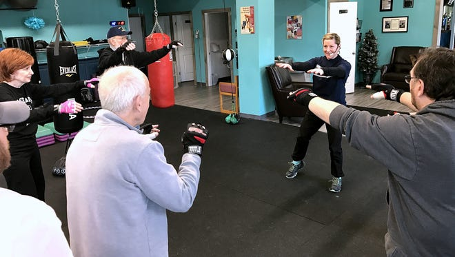 Diane Carozza, right, owner of Di's Personal Fitness in Elmira Heights, leads an exercise class with a group of clients who have Parkinson's disease.